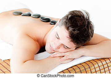 Resting young man lying on a massage table with hot stone on his back in a health spa