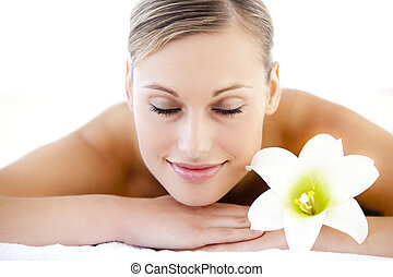 Close-up of a resting woman lying on a massage table with a flower in a spa center