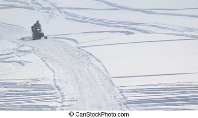 Snowmobile accelerating in the sunshine - Snowmobile with...