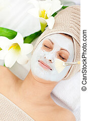 Relaxed woman receiving white cream on her face in a spa...
