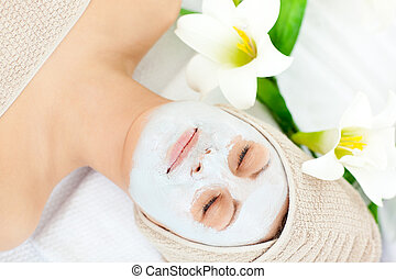 Resting woman with white cream on her face