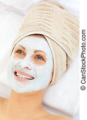 Glowing caucasian woman with white cream on her face