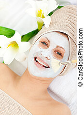Delighted woman receiving white cream on her face in a spa