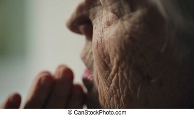 Old woman praying - Old woman with deep wrinkles, prays