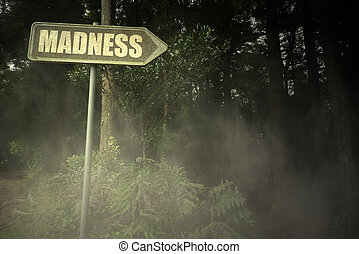 old signboard with text madness near the sinister forest -...