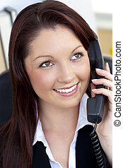 Glowing young businesswoman talking on phone