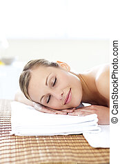 Glowing young woman lying on a massage table
