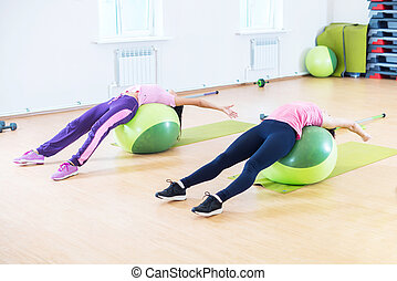 Fit young women stretching backs lying on fitness balls. -...