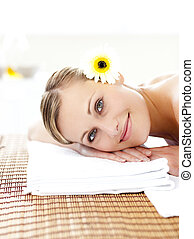 Portrait of an attractive woman lying on a massage table smiling at the camera in a health spa