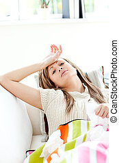 Diseased woman lying on a sofa looking at the camera holding tis