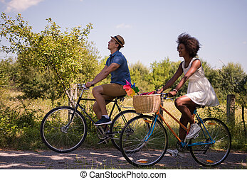 Young multiethnic couple having a bike ride in nature - a...
