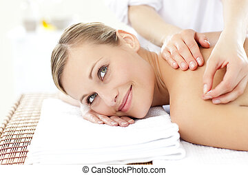 Smiling blond woman receiving an acupuncture treatment in a...