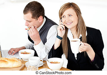 Ambitious businesswoman talking on phone while havin...