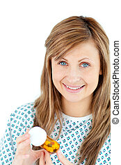 Positive female patient holding pills smiling at the camera