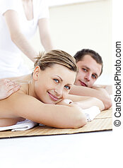 Charming couple smiling at the camera having a back massage