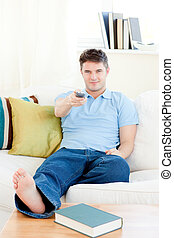 Relaxed young man holding a remote sitting on the couch at...