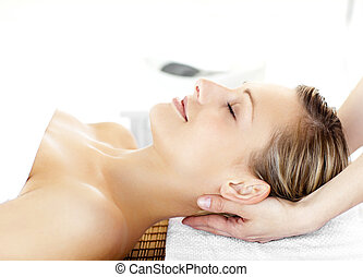 Beautiful young woman  having a massage in a spa center
