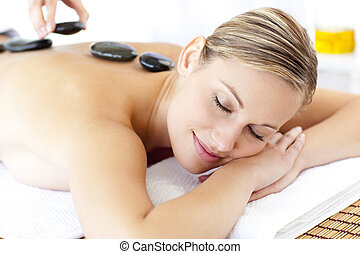 Cute young woman enjoying a back massage with hot stone