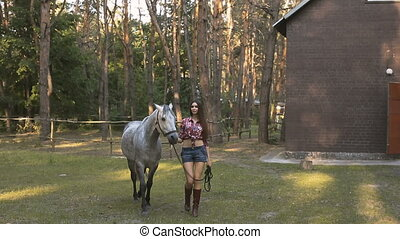 Woman and Horse. Casual Sexy Style - Young cowgirl walking...