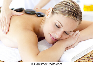Bright young woman enjoying a back massage with hot stone in...