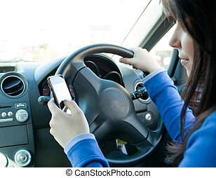 Beautiful brunette woman using her cellphone while driving...
