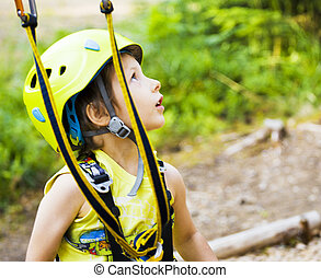 little cute boy in helmet runs track in green forest, happy...