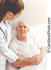 Old man in hospital - Handsome old patient is talking to his...