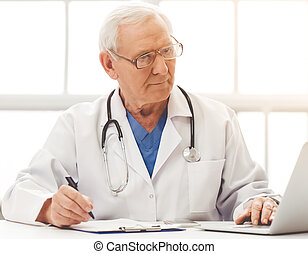 Handsome old doctor in white medical coat and eyeglasses is...