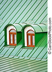 Roof dormers on the roof covered with green iron plates (the...