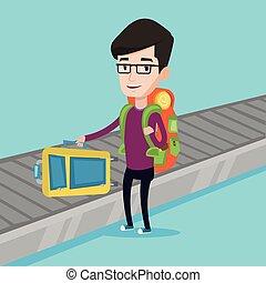 Man picking up suitcase on luggage conveyor belt. -...