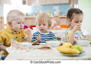 little kids eating in kindergarten