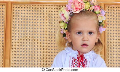 Closeup Little Blond Girl in Garland Chews Candy - closeup...