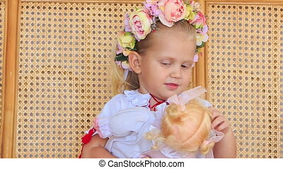 Closeup Little Blond Girl in Garland Sits with Doll -...