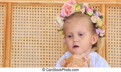 Closeup Little Blond Girl in Garland Chews Candy