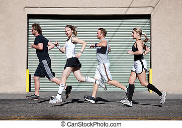 Foursome runs in the city for exercise. - Beautiful,...