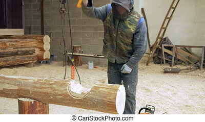 Construction worker cuts a groove in the tree for a future home. Protective mask and headphone on the head of the builder. Hangar with a part of the future home on the background