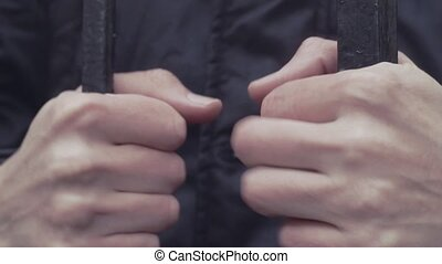young man hand gripping iron bars close up hd