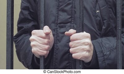 young man hand gripping iron bars close up