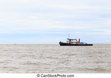 Tug boat was towed ship at the area between the river and...