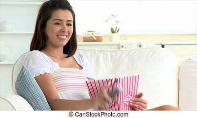 Smiling asian woman eating popcorn sitting on the sofa at...
