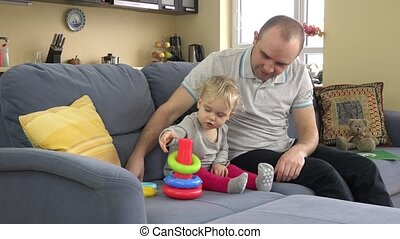 lovely girl and loving father play colorful pyramid rings....