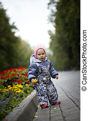 Portrait of child - little girl with fallen leaf walking in autumn park: baby standing in the alley