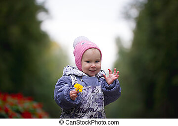 Portrait of child - little girl with fallen leaf walking in autumn park: baby standing in the alley, keep  leaves in hands, waving