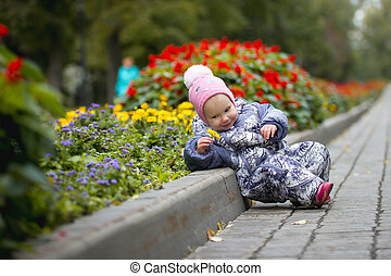 Portrait of child - little girl with fallen leaf walking in autumn park: baby lying in the alley
