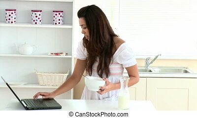 Pretty woman eating cereals using her laptop in the kitchen...