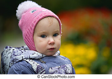 Portrait of child - little girl with fallen leaf walking in park: baby standing at the meadow, close up