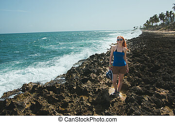 Young woman in in shorts and t-shirt standing on rocks  looking to a sea, the view from the top