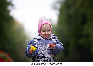 Portrait of child - little girl with fallen leaf walking in autumn park: baby standing in the alley, keep leaves in hands