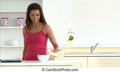 Beautiful asian woman eating cereal