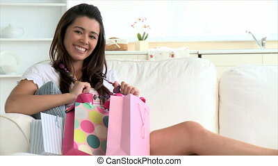 Delighted asian woman holding shopp